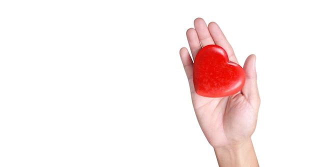Mani che tengono un cuore rosso e concetti di donazione