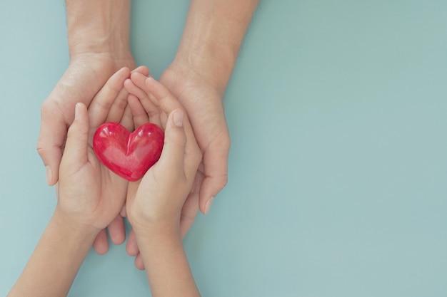 Mani che tengono cuore rosso, concetto di assicurazione sanitaria familiare, giornata mondiale del cuore