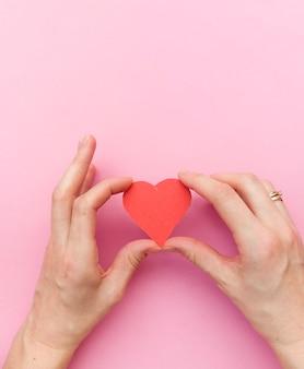 Mani che tengono cuore rosso, salute del cuore, donazione, beneficenza volontaria felice, responsabilità sociale della rsi, giornata mondiale del cuore, giornata mondiale della salute, giornata mondiale della salute mentale, casa adottiva, benessere, concetto di speranza