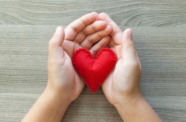 Mani che tengono un cuore rosso di feltro.