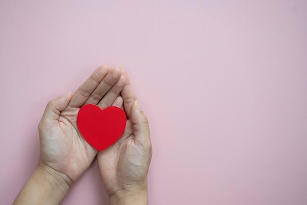 Mani che tengono cuore rosso su sfondo rosa pastello copia spazio