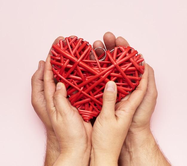 Mani che tengono un cuore rosso