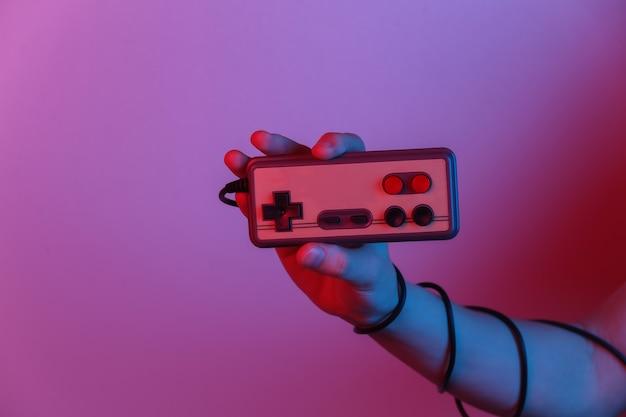 Mani che tengono il joystick retrò in luce sfumata al neon blu-rosso. vecchio gioco. onda retrò anni '80. minimalismo