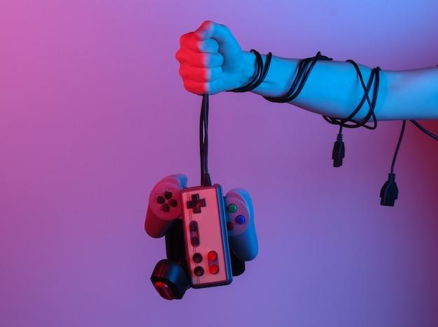 Mani che tengono il joystick retrò tramite cavo in luce sfumata al neon blu-rosso. vecchio gioco. onda retrò anni '80. minimalismo
