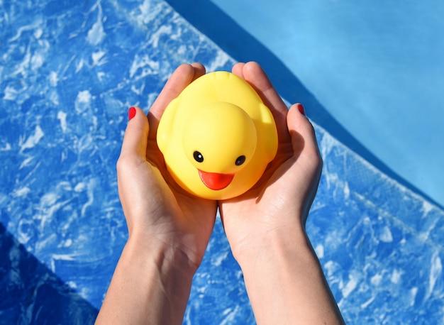 Mani che tengono anatra di gomma sul fondo della piscina