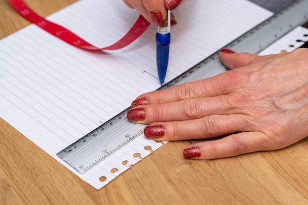 Mani che tengono un righello e una penna che misurano e ricalcano su carta, preparando il progetto artistico
