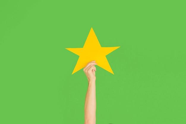 Mani che tengono il segno della stella su sfondo verde studio