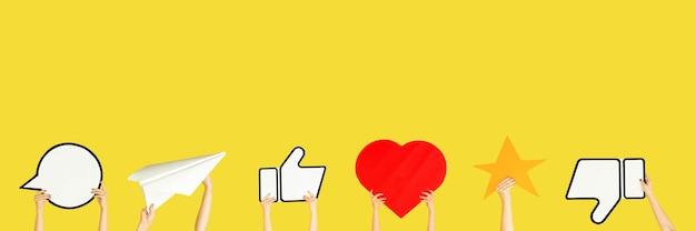 Mani che tengono i segni dei social media sul volantino giallo dello sfondo dello studio copyspace