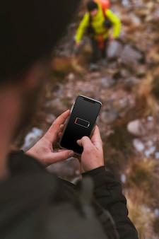 Mani che tengono uno smartphone all'aperto