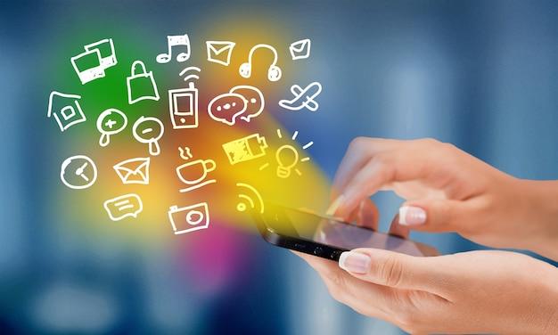 Mani che tengono smartphone con icone multimediali disegnate a mano e simboli concept
