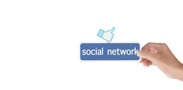 Mani che tengono il servizio di social network stampato su carta