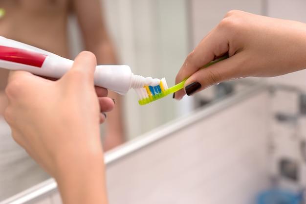 Mani che tengono uno spazzolino da denti e ci mettono sopra del dentifricio davanti allo specchio nel moderno bagno piastrellato