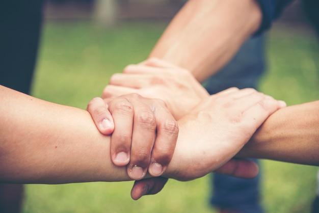 Mani che tengono fiducia a vicenda con il concetto di associazione di successo soci commerciali che si tengono per mano insieme come triangolo