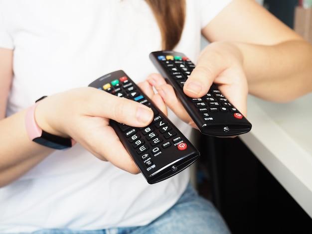 Mani che tengono il telecomando della tv, primo piano a casa.