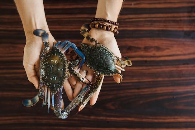 Mani che tengono due granchi freschi colorati sul fondo della tavola in legno prima della cottura. vista dall'alto con copia spazio