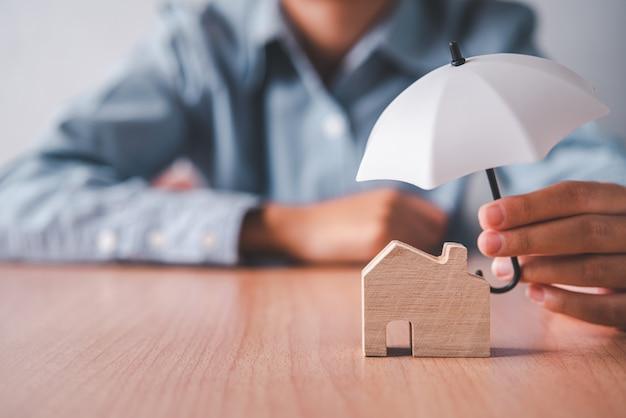 Mani che tengono un ombrello su una casa di legno. concetto di assicurazione sulla casa, assistenza domiciliare e sicurezza.