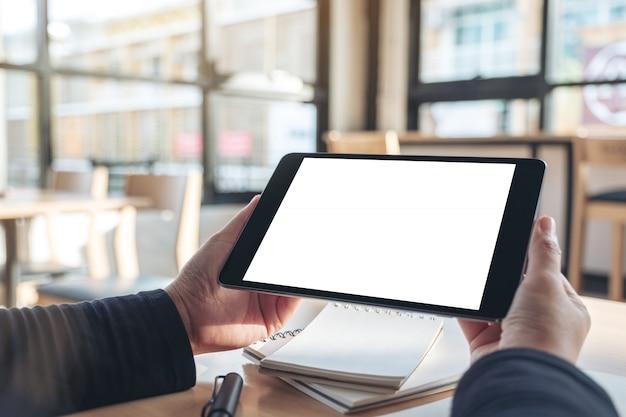 Mani che tengono e utilizzando tablet pc nero con schermo desktop bianco vuoto mentre si lavora su notebook in ufficio