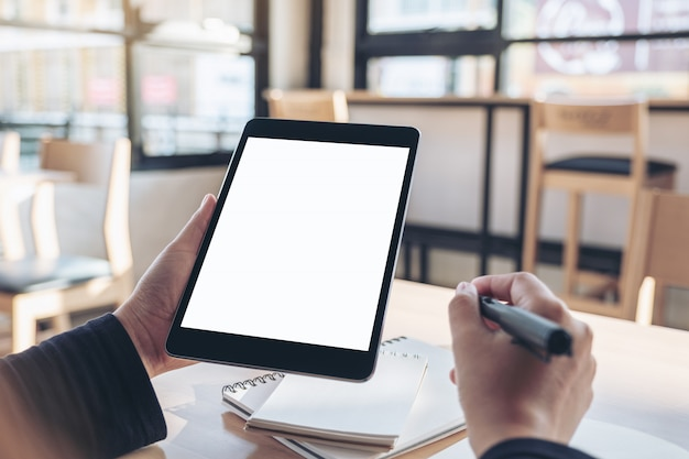Mani che tengono e utilizzando tablet pc nero con schermo del desktop bianco vuoto mentre si scrive su notebook in ufficio