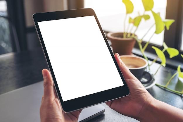 Mani che tengono e utilizzando tablet pc nero con schermo desktop bianco vuoto con notebook, foglie verdi e tazza di caffè sulla tavola di legno