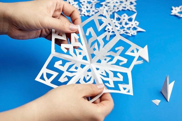 Mani che tengono il fiocco di neve di carta tagliata bianca sulla superficie blu