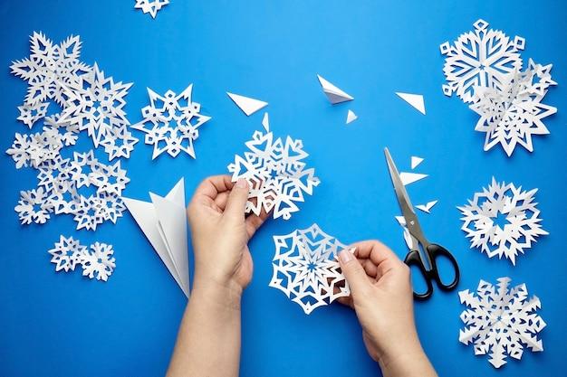 Mani che tengono i fiocchi di neve di carta tagliati bianchi sulla superficie blu