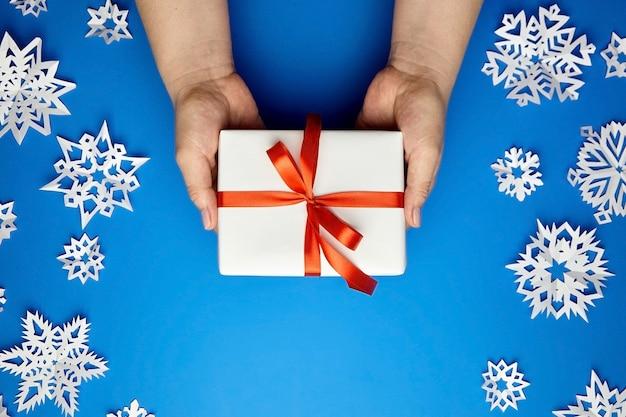 Mani che tengono il contenitore di regalo bianco con il nastro rosso sull'azzurro con i fiocchi di neve di carta