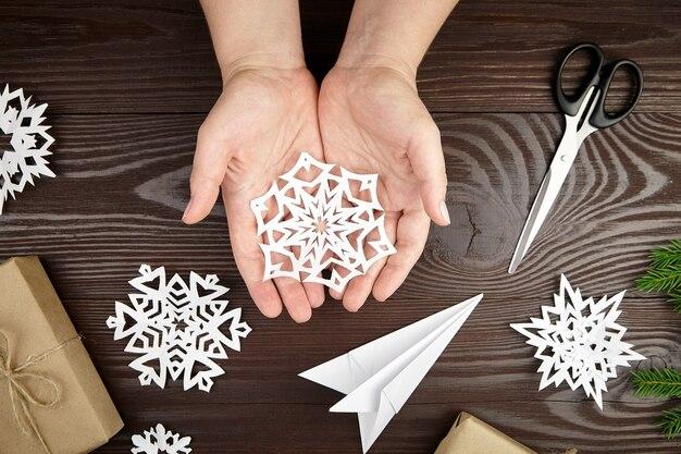 Mani che tengono il fiocco di neve del libro bianco sulla tavola di legno