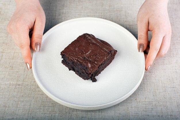 Mani che tengono un piatto bianco con un pezzo di biscotto