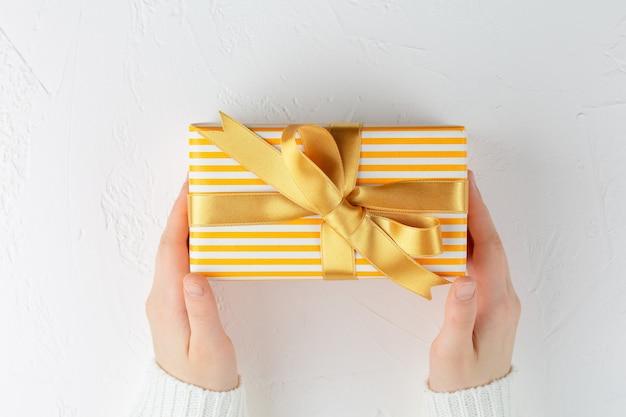 Mani che tengono il contenitore di regalo giallo