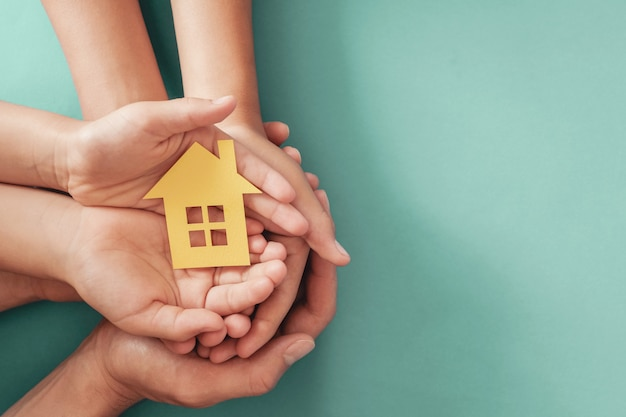 Mani che tengono la casa di carta gialla su superficie blu, casa di famiglia, alloggio di alloggio senza tetto e assicurazione di protezione domestica, concetto di ipoteca, assistenza domiciliare adottiva