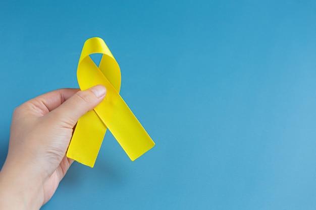 Mani che tengono nastro giallo, simbolo di consapevolezza del cancro, supporto medico e prevenzione con la mano d'aiuto. su