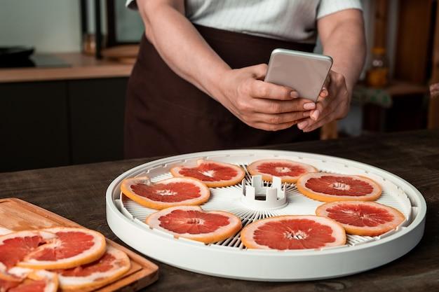 Mani della casalinga con lo smartphone sopra il vassoio rotondo dell'essiccatore di frutta con pompelmo affettato fresco sul tavolo mentre si fa la foto di loro