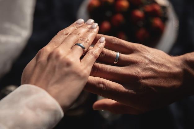 Mani di marito e moglie con fedi nuziali