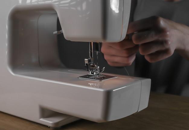 Mani che inseriscono il filo attraverso il foro dell'ago nei dettagli della macchina da cucire
