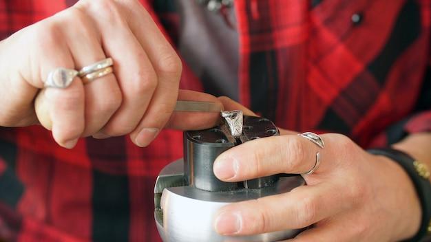 Mani di un gioielliere close-up, creazione di gioielli. primo piano del lavoro del gioielliere.