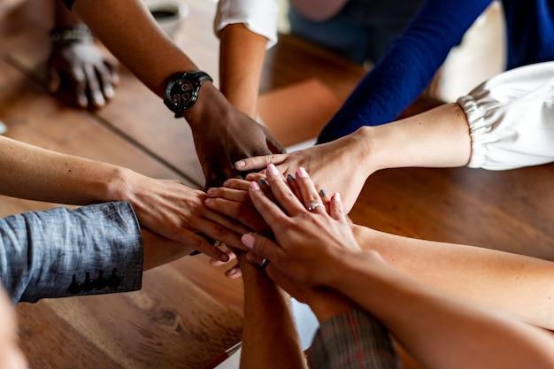 Mani giunte su un tavolo di legno