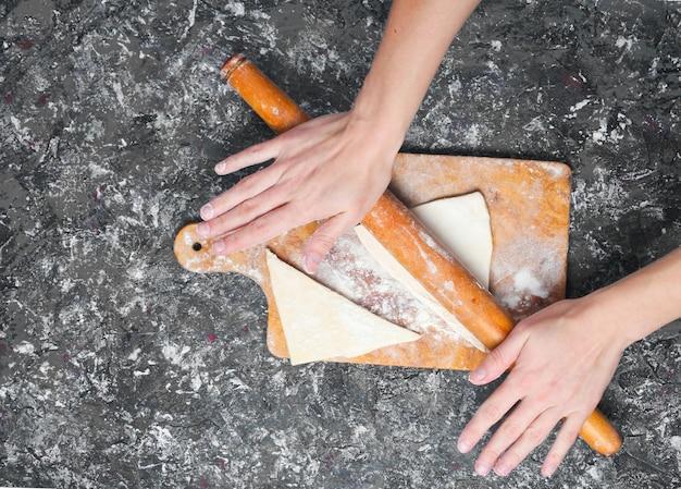 Le mani tengono il mattarello e rotolano la pasta sul tavolo di cemento grigio