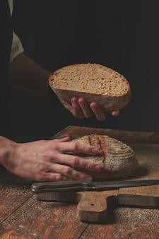 Mani che tengono la pagnotta di pane al forno su sfondo scuro