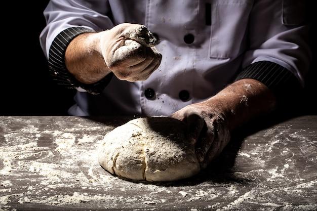 Mani che impastano pasta cruda culinaria, cucina, forno