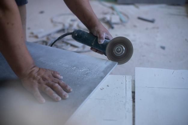 Mani dell'operaio latino che tagliano con una smerigliatrice elettrica