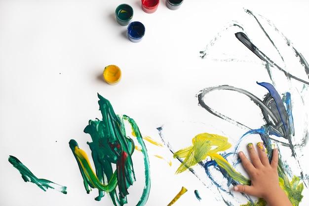 Mani di una pittura del ragazzino con gli acquerelli sullo strato del libro bianco. ragazzino con un pennello e vernici.