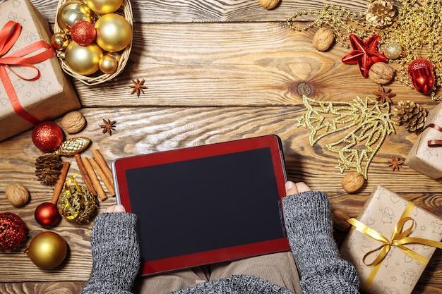 Mani di un bambino piccolo con computer tablet vicino a decorazioni natalizie e regali