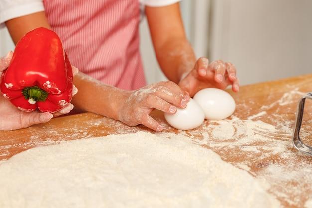 Le mani di una bambina che prepara la pasta in cucina si chiudono