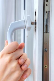 Mani fabbro rimuovere la maniglia del telaio della finestra, close-up.