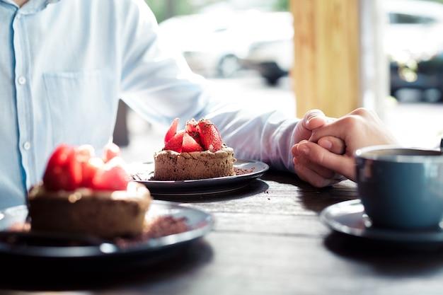 Mani di una coppia di innamorati a un tavolo in un caffè