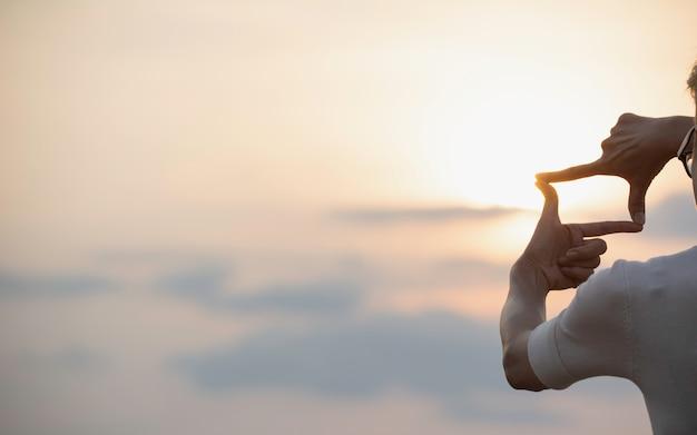 Mani facendo cornice con il tramonto. chiuda su delle mani della donna che fanno il gesto della struttura.