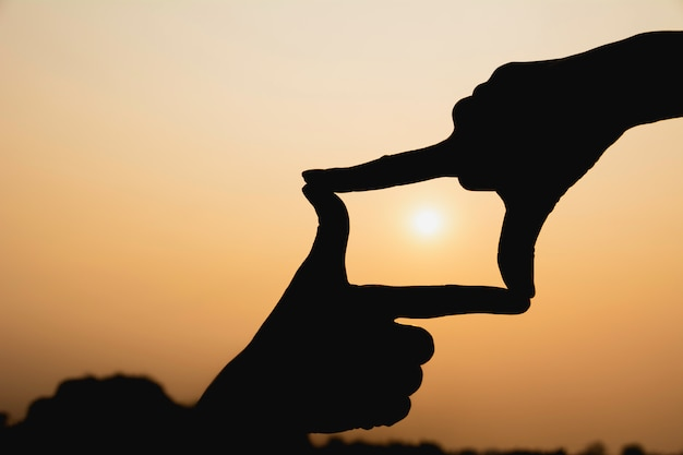 Mani facendo cornice con il tramonto