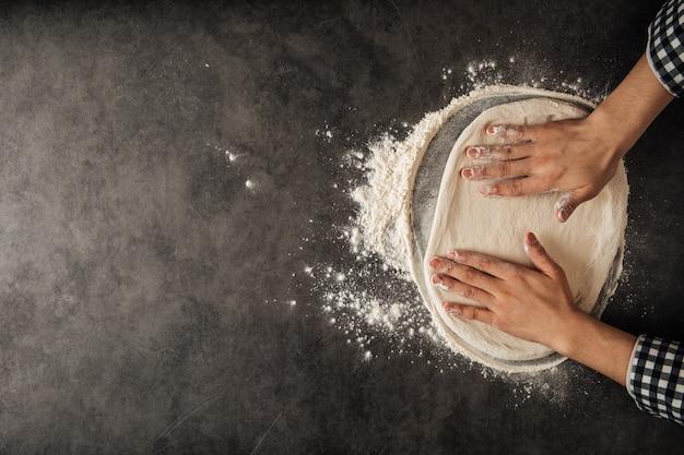 Mani che fanno una pasta per pizza con farina sullo sfondo grigio cemento