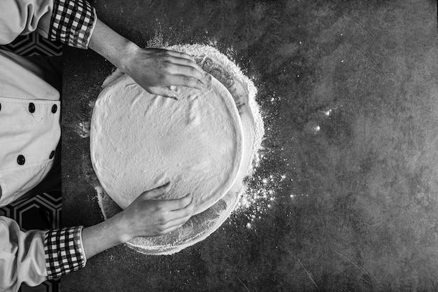 Mani che preparano un impasto per pizza con la farina