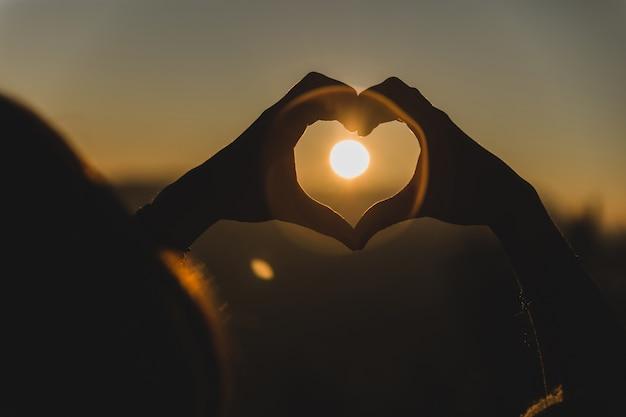 Le mani la forma di un cuore con il sole nel mezzo